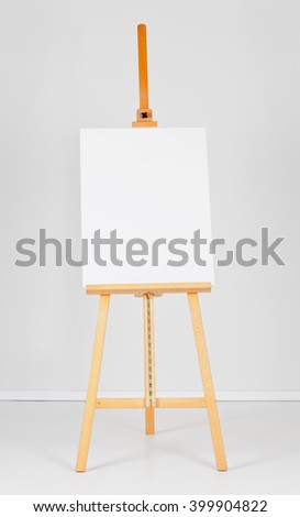 Wooden easel with blank canvas in front of white wall - stock photo