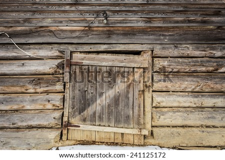Wooden entrance door of an old wooden house with a light bulb over the entrance