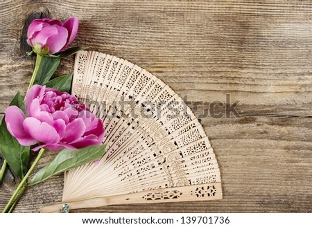 Wooden fan and pink peony on wooden background. Copy space. - stock photo
