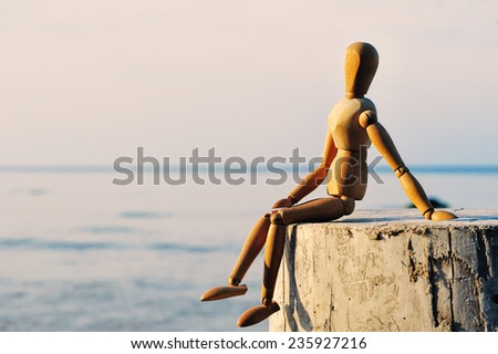 Wooden female figure sitting on the stump at the sea - stock photo