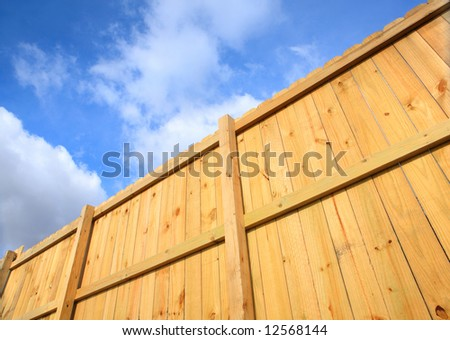 Wooden Fence against a blue cloudy sky - stock photo