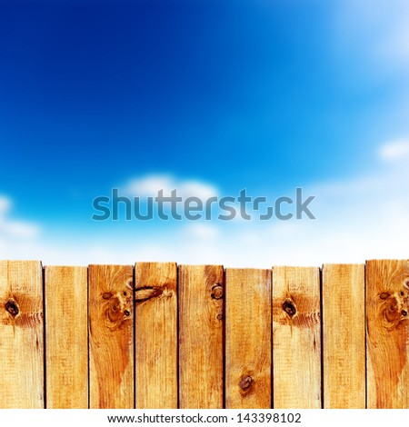 Wooden fence against blue sky background - stock photo
