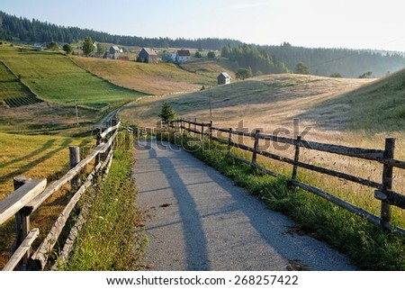 wooden fence and countryside road in Durmitor National Park, Montenegro - stock photo