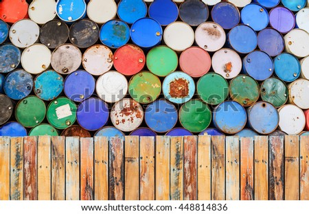 Wooden fence and old oil barrels stacked up in a warehouse - stock photo