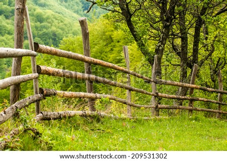 Wooden fence in countryside with grass  - stock photo
