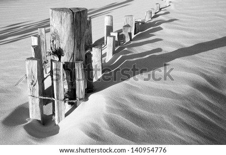Wooden fence in sand dunes with strong shadows from sunlight - stock photo