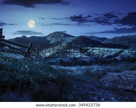 wooden fence in the grass on the hillside near the village at night in full moon light - stock photo