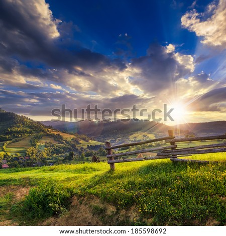 wooden fence in the grass on the hillside near the village at sunset - stock photo