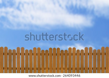 wooden fence on a blue sky background - stock photo