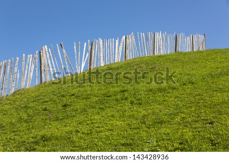 Wooden fence on a grass covered hill