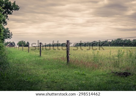 Wooden fence on a green field in cloudy weather - stock photo