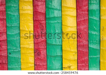 Wooden fence painted in yellow, green, red - stock photo