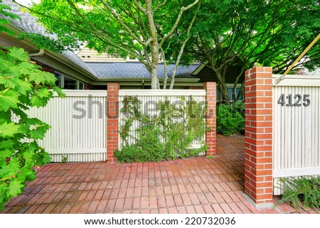 Wooden fence with brick columns. House with tile floor front yard - stock photo