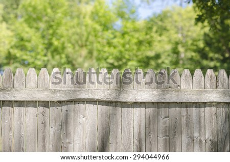 Wooden Fence With Copy Space Above During Summer. Top of a wooden old, classical fence with copy space above with trees and sky in background. - stock photo