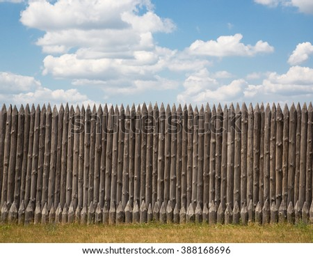 Wooden fence with pointed tips on a background of blue sky with clouds