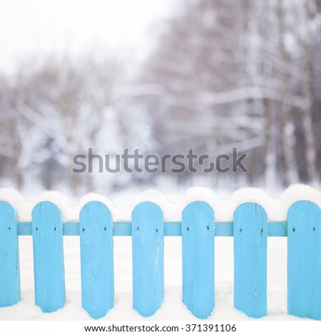 Wooden fence with snow on blurred winter forest background - stock photo
