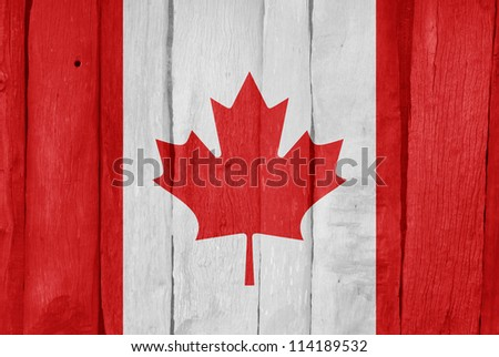 Wooden fence with the flag of Canada painted on it - stock photo