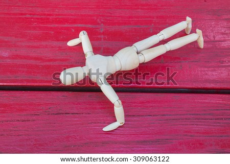 Wooden figure exercise on redwood-wall - stock photo