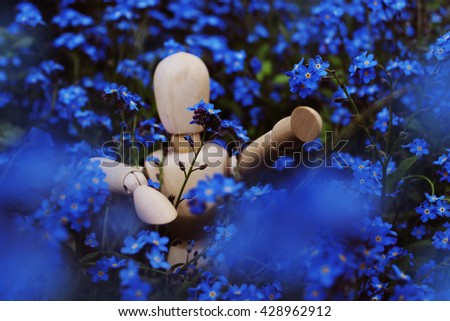 Wooden figurine in blue flowers - stock photo