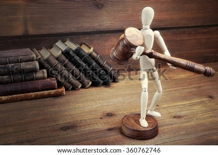 Wooden Figurine With Judges Gavel  And Old Law Book On The Rough Wood Table Background - stock photo