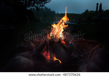 Wooden fire pit in the moonlight by the lake shore