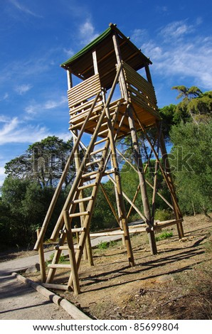 Wooden fire-watch high tower in a hill surrounded by trees - stock photo