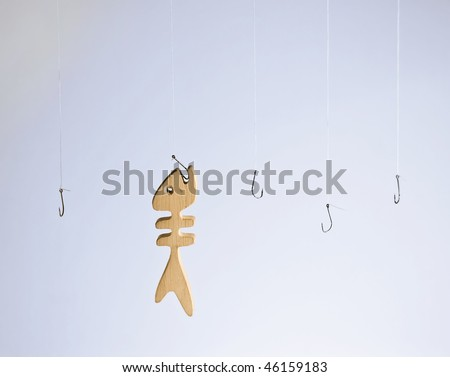 Wooden fish caught on one hook among other empty ones - stock photo