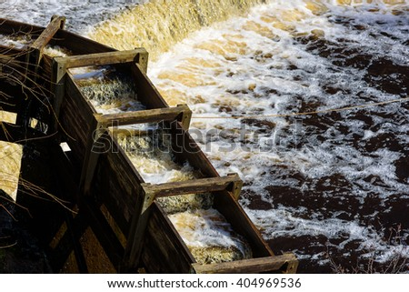 Wooden fish ladder with flowing water beside a reservoir overflow. This helps migrating fish to navigate obstacles in the main waterway. Lyckeby, Sweden.