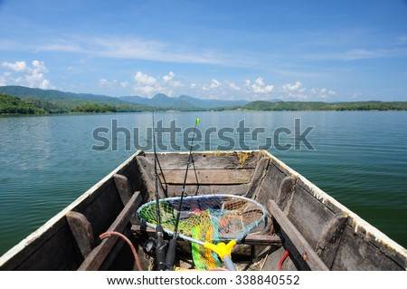 Wooden fishing boat with fishing rod heading to the lake - stock photo