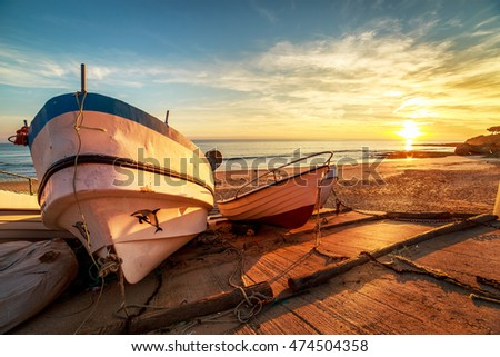 Wooden fishing boats in a small port on the beach in sunset light