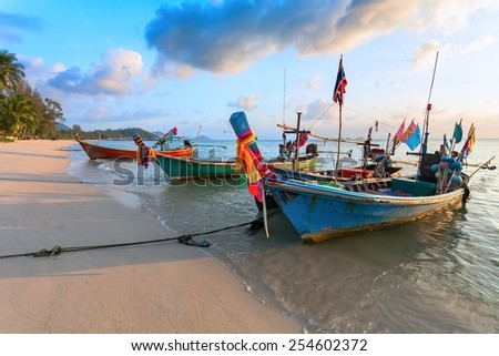 Wooden fishing boats on the sandy shores of the sea (Thailand) - stock photo