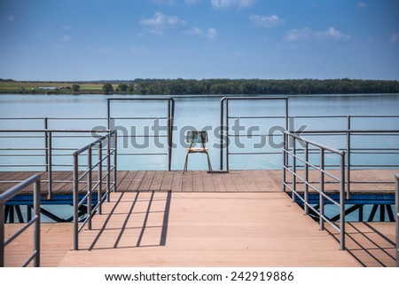 Wooden fishing pier on a beautiful lake with one chair in the middle