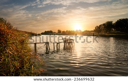 Wooden fishing sigean at sunset in autumn - stock photo