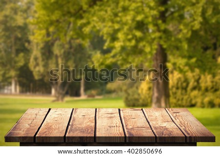 Wooden Floor against trees and meadow - stock photo
