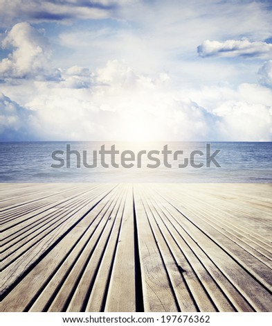 Wooden floor leading to sea and sky  - stock photo