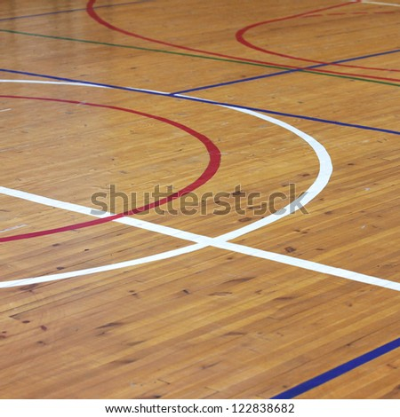 Wooden floor of sports hall with marking lines - stock photo