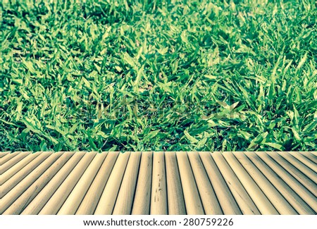 wooden floor on fresh grass in day light background in vintage tone - stock photo