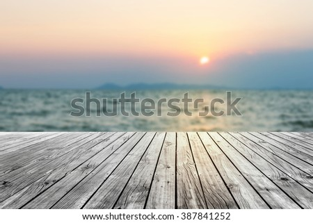 Wooden floor with blur sea at sunset - stock photo