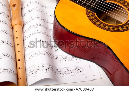 Wooden flute and classic acoustic guitar on sheet music. Close up. - stock photo