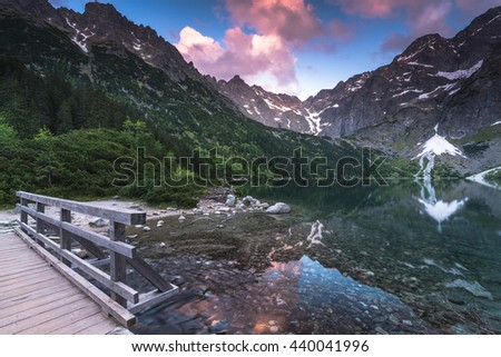 wooden foot bridge in hing mountains over lake with dramatic sky at sunset - stock photo