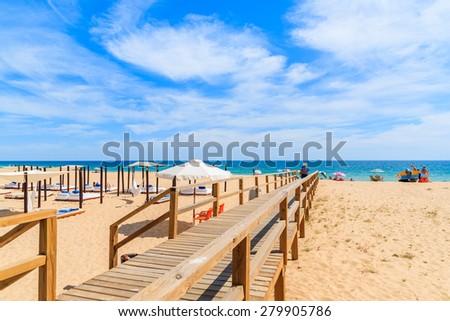 Wooden footbridge to sandy beach in Armacao de Pera coastal town, Algarve region, Portugal - stock photo