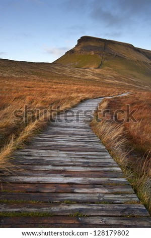 Wooden footpath over bog land leading ot Pen-y-Ghent in Yorkshire Dales National Park - stock photo
