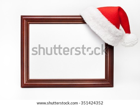 Wooden frame for paintings with a Christmas cap on a white background - stock photo