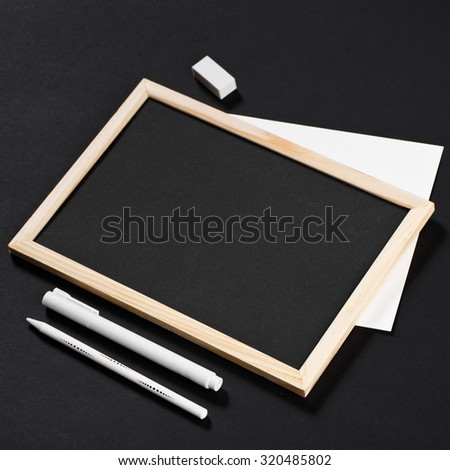 wooden frame with black field with marker and white pencil and eraser on black paper. Mockup. Real photo for you text