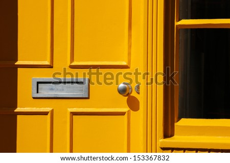 Wooden front door (doorway) in Traditional Georgian architecture freshly painted in yellow color. - stock photo
