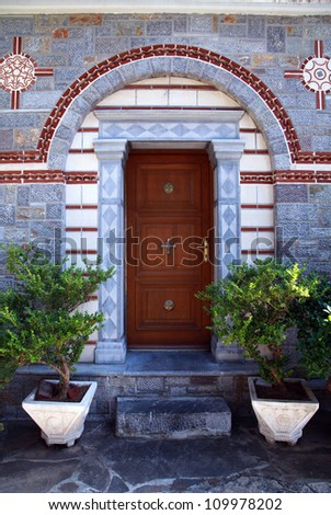 Wooden front door entrance in ornate stone house(Greece) - stock photo