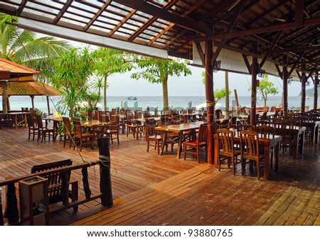 Wooden furniture in beachfront cafe. - stock photo