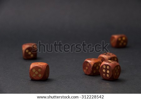 Wooden gambling dices on black background. - stock photo