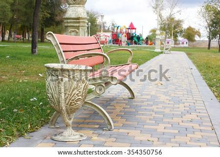 Wooden garden bench in a city park - stock photo