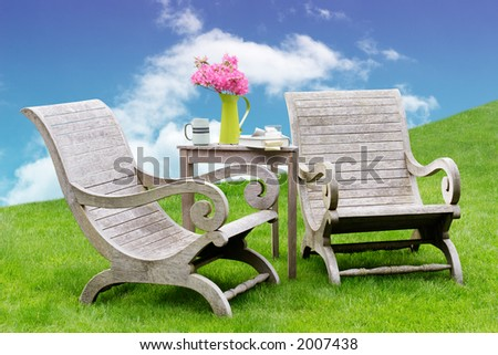 Wooden garden chairs in a green spot in the garden - stock photo